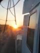 Die untergehende Sonne im kaputten Rueckspiegel des Trucks auf dem Weg nach Divundu
